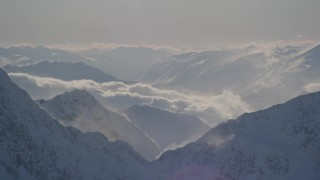 AK0001_1977 - 4K stock footage aerial video snowy, windblown mountain ranges and low clouds in Kenai Mountains, Alaska
