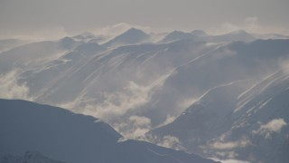 AK0001_1980 - 4K stock footage aerial video snow covered, windblown Kenai Mountains and low clouds, Alaska