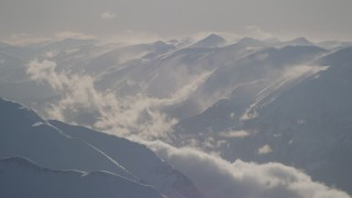 AK0001_1981 - 4K stock footage aerial video snow covered, windswept Kenai Mountains, Alaska