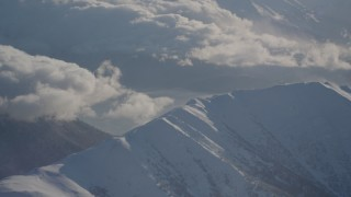 AK0001_1985 - 4K stock footage aerial video cloudy Kenai Mountains, snow covered, windblown Chugach Mountains, Alaska