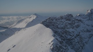 AK0001_1991 - 4K stock footage aerial video flying over a snow covered mountain ridge in the Chugach Mountains, Alaska