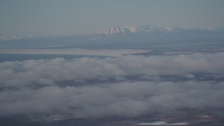 AK0001_2003 - 4K stock footage aerial video snowy Mount Susitna near Point MacKenzie, clouds covering Anchorage, Alaska