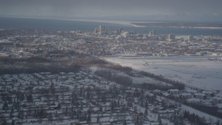 AK0001_2011 - 4K stock footage aerial video flying over snowy neighborhoods toward Downtown Anchorage, Alaska
