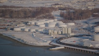 AK0001_2031 - 4K stock footage aerial video flying away from a snow covered oil refinery in Anchorage, Alaska
