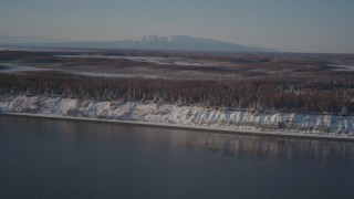 AK0001_2033 - 4K stock footage aerial video flying over snowy, wooded shore of Point MacKenzie, Alaska