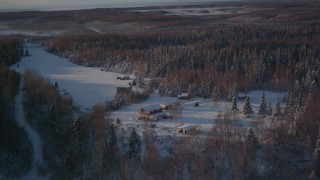 AK0001_2037 - 4K stock footage aerial video flying away from cabins in snowy woods in Point MacKenzie, Alaska