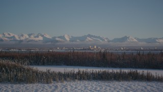 AK0001_2038 - 4K stock footage aerial video cloudy Chugach Mountains, snowy forest, Downtown Anchorage, Alaska