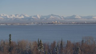AK0001_2039 - 4K stock footage aerial video cloudy Chugach Mountains, snowy wooded shore, Downtown Anchorage, Alaska