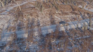 AK0001_2044 - 4K stock footage aerial video flying toward a rural highway in Point MacKenzie, Alaska in snow