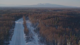 AK0001_2045 - 4K stock footage aerial video following a deserted snowy rural highway in Point MacKenzie, Alaska