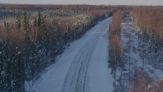 AK0001_2047 - 4K stock footage aerial video following a deserted rural snow covered highway in Point MacKenzie, Alaska