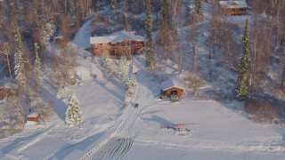 AK0001_2049 - 4K stock footage aerial video a house and helicopter in a snowy forest in Big Lake Area, Alaska