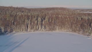 AK0001_2050 - 4K stock footage aerial video flying over frozen lakes, snowy forest in Big Lake Area, Alaska