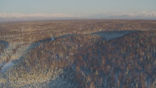 AK0001_2067 - 4K stock footage aerial video flying over houses surrounded by snowy forest in Knik-Fairview at sunset, Alaska