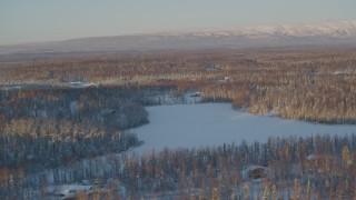 AK0001_2068 - 4K stock footage aerial video houses near frozen lake, snowy forest in Knik-Fairview, Alaska, sunset