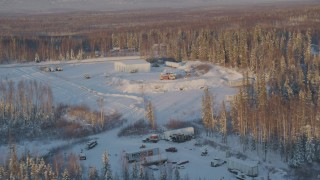 AK0001_2069 - 4K stock footage aerial video approach building surrounded by snowy forest in Knik-Fairview, Alaska, sunset