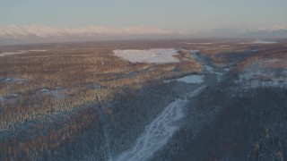 AK0001_2072 - 4K stock footage aerial video flying over snowy forest toward Shawn Field at sunset, Wasilla, Alaska