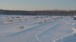AK0001_2074 - 4K stock footage aerial video flying by parked aircraft at snow covered Shawn Field at sunset, Wasilla, Alaska
