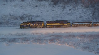 AK0001_2078 - 4K stock footage aerial video tracking a train running through snowy forest at sunset, Wasilla, Alaska