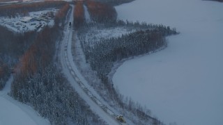 AK0001_2081 - 4K stock footage aerial video a snow covered train running around Jacobsen Lake at twilight, Wasilla, Alaska