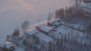 AK0001_2084 - 4K stock footage aerial video orbiting a snow covered house on Lucile Lake at sunset, Wasilla, Alaska
