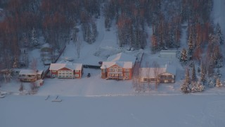 AK0001_2086 - 4K stock footage aerial video flying away from snow covered houses on Lucile Lake at sunset, Wasilla, Alaska
