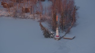 AK0001_2089 - 4K stock footage aerial video snowy Cottonwood Lake, descend toward lighthouse, Wasilla, Alaska, sunset