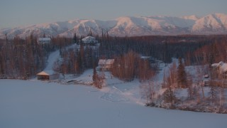 AK0001_2090 - 4K stock footage aerial video fly by snow covered homes on frozen Cottonwood Lake, Wasilla, Alaska, twilight