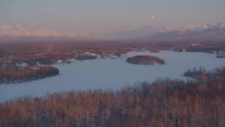 AK0001_2091 - 4K stock footage aerial video snowy, wooded shore of Cottonwood Lake, Finger Lake, Wasilla, Alaska, twilight