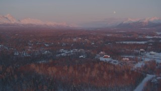 AK0001_2093 - 4K stock footage aerial video over snow covered homes, Walby Lake, reveal mountains, Palmer, Alaska, twilight