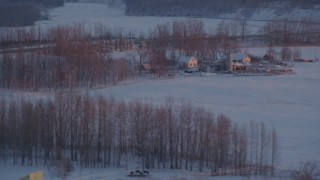 AK0001_2096 - 4K stock footage aerial video passing a rural home with snow on the ground at twilight, Palmer, Alaska