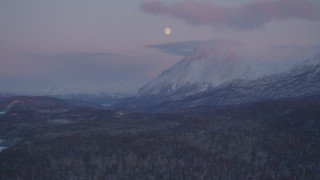 AK0001_2107 - 4K stock footage aerial video the moon over the snow covered Chugach Mountains at twilight, Alaska