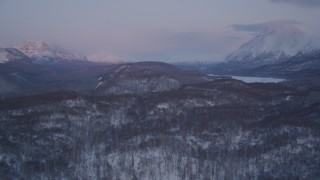 AK0001_2109 - 4K stock footage aerial video snowy, wooded hills, Matanuska River Valley, Chugach Mountains, Alaska, sunset