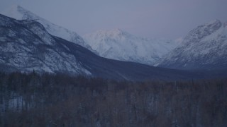 AK0001_2113 - 4K stock footage aerial video flying by snowy, forested hills, snowy Talkeetna Mountains at twilight, Alaska