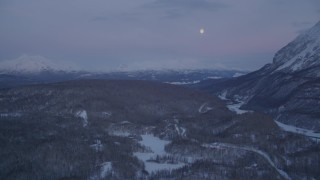 AK0001_2114 - 4K stock footage aerial video snowy Thirtymile Lake, moon over snowy Talkeetna Mountains, Alaska, twilight