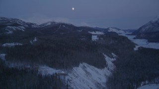 AK0001_2120 - 4K stock footage aerial video reveal moon over snow covered Talkeetna Mountains at twilight, Sutton, Alaska
