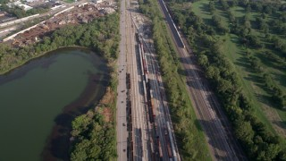 AX0001_006 - 5K stock footage aerial video flying over Burnham Woods Golf Course, revealing a train yard and Powder Horn Lake, Illinois