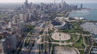AX0001_020 - 5K stock footage aerial video tilt from Highway 41 to reveal Soldier Field and Downtown Chicago skyline, on a hazy day, Illinois