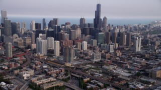 AX0001_065 - 5K stock footage aerial video tilting up from heavy traffic on Interstate 90 and 94, revealing Downtown Chicago skyscrapers, Illinois