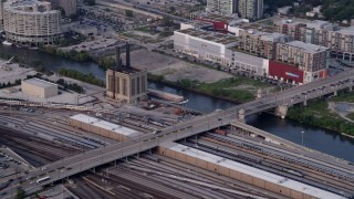 AX0001_073 - 5K stock footage aerial video of reverse view of a barge chugging down the Chicago River, Illinois, seen from a riverfront train yard