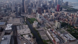 AX0001_078 - 5K stock footage aerial video tilting from Metra Railroad Yard and Chicago River, reveal hazy Downtown Chicago, Illinois