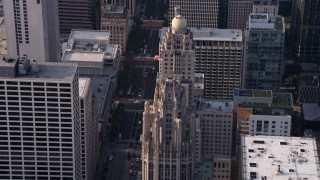 AX0001_118 - Aerial stock footage of 5K aerial  video approach flag flying at top of Tribune Tower in Downtown Chicago, Illinois
