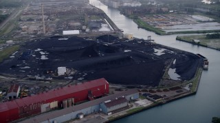 AX0001_169 - Aerial stock footage of 5K aerial  video approach petroleum coke piles by the Calumet River, East Side Chicago, Illinois