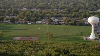 AX0001_178 - 5K stock footage aerial video players playing football at Thornton Fractional South High School in Lansing, on a hazy day, Illinois