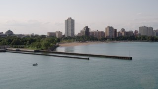 AX0002_002 - 5K stock footage aerial video flying over piers on Lake Michigan toward a beach and apartment buildings in Hyde Park, Chicago, Illinois