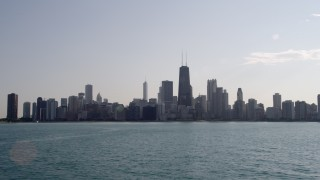 AX0002_019 - 5K stock footage aerial video fly low over Lake Michigan and tilt to reveal the skyline of Downtown Chicago, Illinois