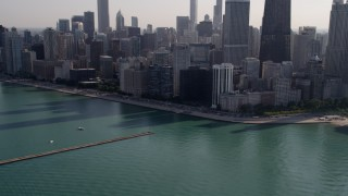 AX0002_022 - 5K stock footage aerial video tilt from Lake Michigan revealing John Hancock Center and Downtown Chicago skyscrapers, Illinois