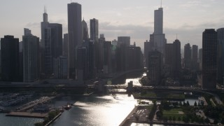 AX0002_051 - 5K stock footage aerial video approach skyline and bridge over Chicago River, with sun reflecting on water, Downtown Illinois