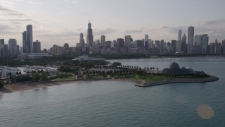 AX0002_088 - 5K stock footage aerial video of the Downtown Chicago skyline seen while flying by Adler Planetarium, Illinois