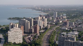 AX0002_094 - 5K stock footage aerial video of following train tracks by Hyde Park apartment buildings, Chicago, Illinois